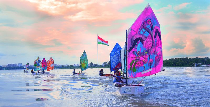 Young sailors practicing at Hussain Sagar with sails rendered in art