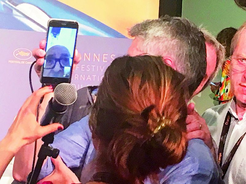 Journalists interview Godard via phone.