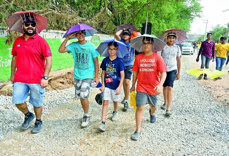 Cricket enthusiasts walk towards the Uppal stadium with cardboard hats and umbrellas to escape the scorching heat in the gallery. ( Image: P. SURENDRA)