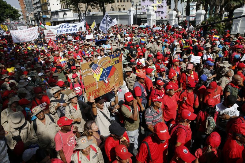 Members of the Bolivarian Militia and supporters of Venezuela's President Nicolas Maduro particiapte in a rally outside Miraflores presidential palace in Caracas, Venezuela, Monday, May 20, 2109. Maduro is celebrating the anniversary of his disputed re-election amid a growing humanitarian crisis and political upheaval. (AP Photo/Ariana Cubillos)