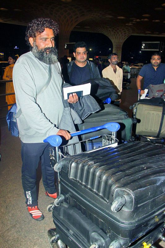 A priest accompanies the Sharma family at the  airport; (right) Anushka Sharma's brother Karnesh