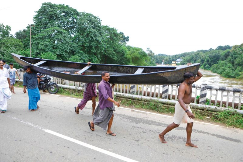 People carry a country boat to other side of Meenachil river through Mutholi bridge for rescue operations near Pala in Kottayam on Friday (Photo: RAJEEV PRASAD)