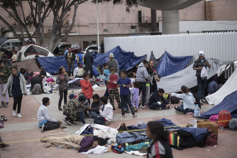 In this Monday, April 30, 2018 file photo, Migrants wait for access to request asylum in the U.S., at the El Chaparral port of Entry in Tijuana, Mexico, Top officials from the U.S. and Mexico will begin talks Monday, June 3, 2019 in a scramble to fend off President Donald Trump s threat of devastating tariffs and meet his demand for fewer migrants at the border. (AP Photo/Hans-Maximo Musielik, File)