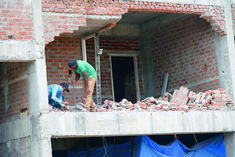 Workers without safety gear drill holes and place explosives to implode the illegal building.