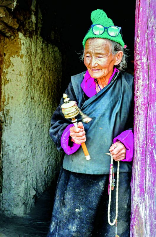 A woman silently mumbles while rotating her prayer wheels in the monastery of Lamayuru in Ladakh.