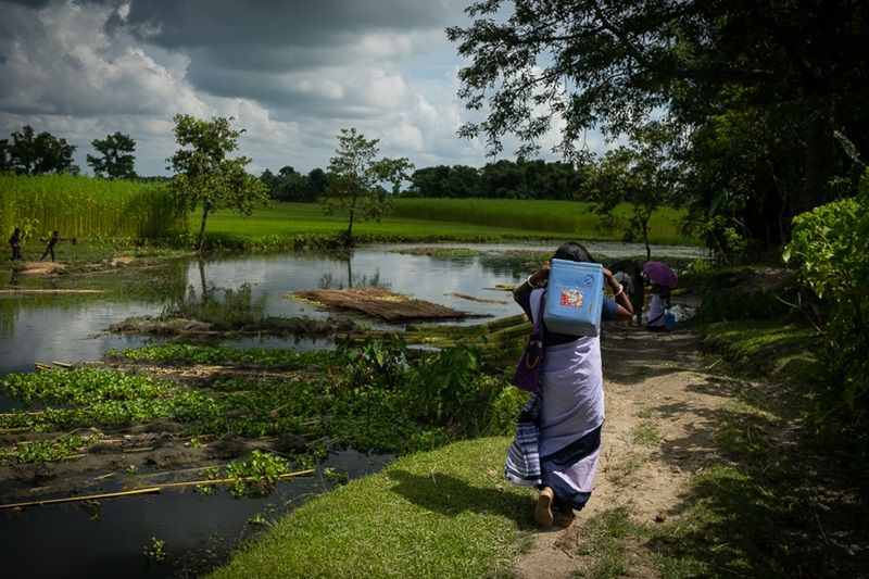 The ASHA workers continue without a break, wading through waterbodies and shifting the weight of the vaccine carriers from one shoulder to another. (Photo: MoHFW)
