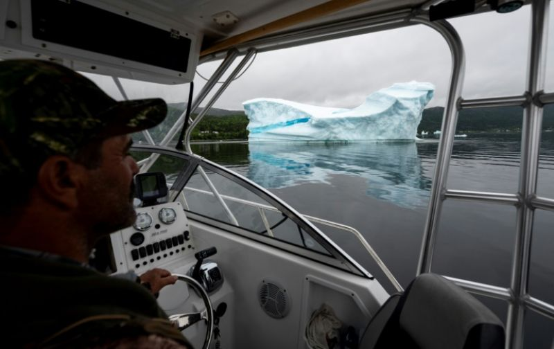 Tour guide and former fisherman Barry Strickland steers his boat near an iceberg at King's Point -- iceberg tourism has been a success for the area on Canada's eastern shores. (Photo: AFP)