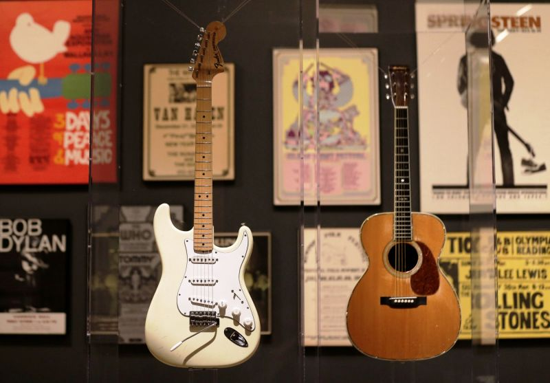 Guitars used by Jimi Hendrix (L) and Eric Clapton are displayed with concert posters at the exhibit. (Photo: AP)