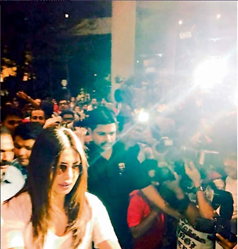 ) A picture showing PeeCee being mobbed at the Mumbai airport, after she returned to India from the US