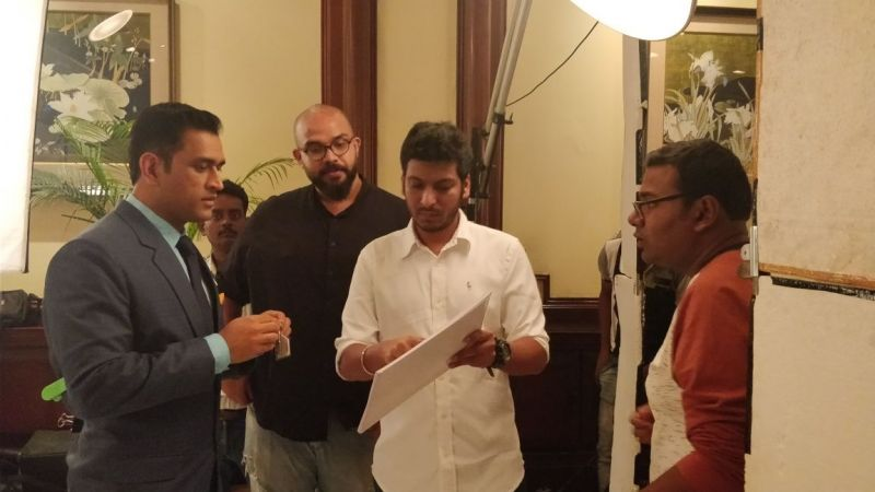 Abhisek looks on while Mahendra Singh Dhoni gears up for the shoot.
