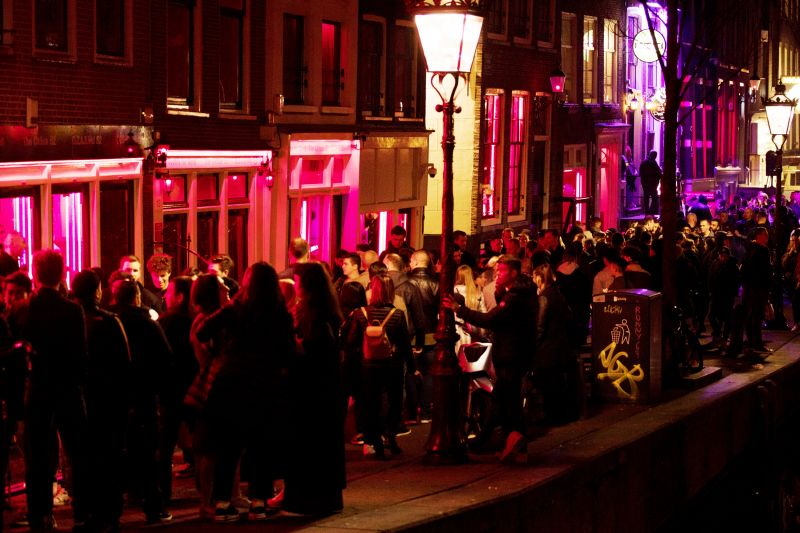 Tourists bathing in a red glow emanating from the windows and peep shows' neon lights, packed shoulder to shoulder as they shuffle through the alleys in Amsterdam's red light district. (Photo: AP)