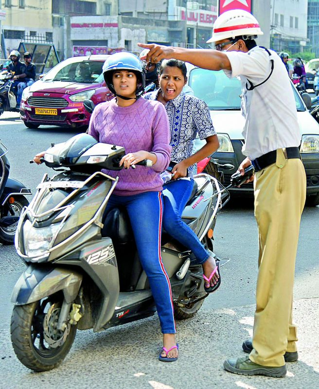 Women on a two-wheeler try to make a point with with a traffic cop to let them through.