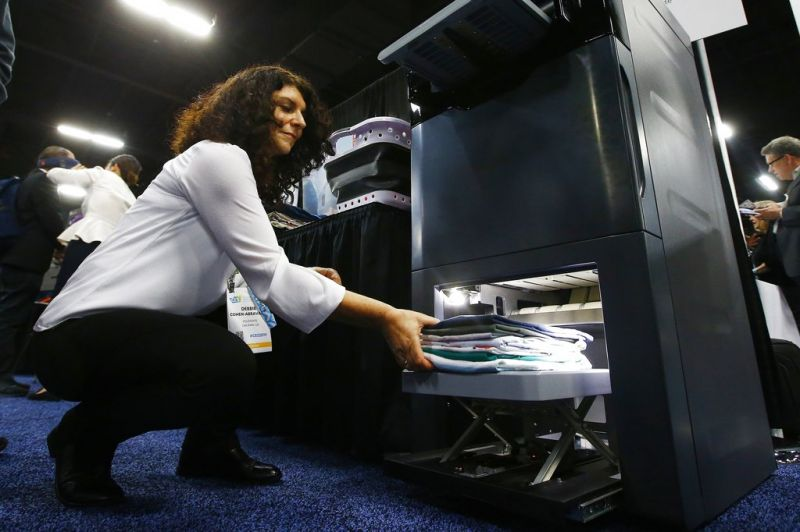 Debbie Cohen-Abravanel, CMO at Foldimate, demonstrates the new device that folds your clothes automatically, at the CES Unveiled at CES International, Sunday, Jan. 6, 2019, in Las Vegas. (AP Photo/Ross D. Franklin)