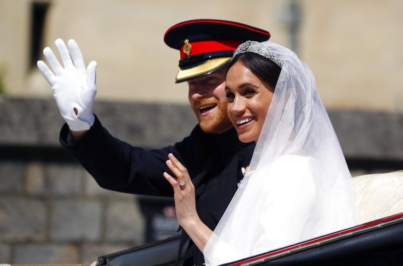 Britain's Prince Harry and his wife Meghan Markle ride a horse-drawn carriage, after their wedding ceremony. (Photo: AP)
