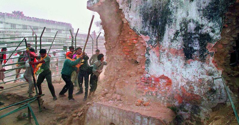 Hindu fundamentalists attack the wall of the 16th century Babri Masjid with iron rods on December 6, 1992  —AFP