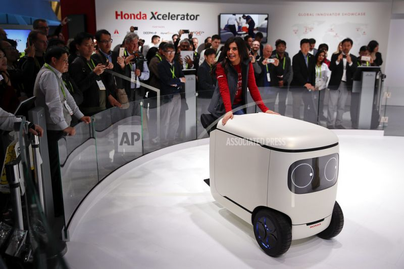 An exhibitor demonstrates the Honda robotics concept 3E-C18.
