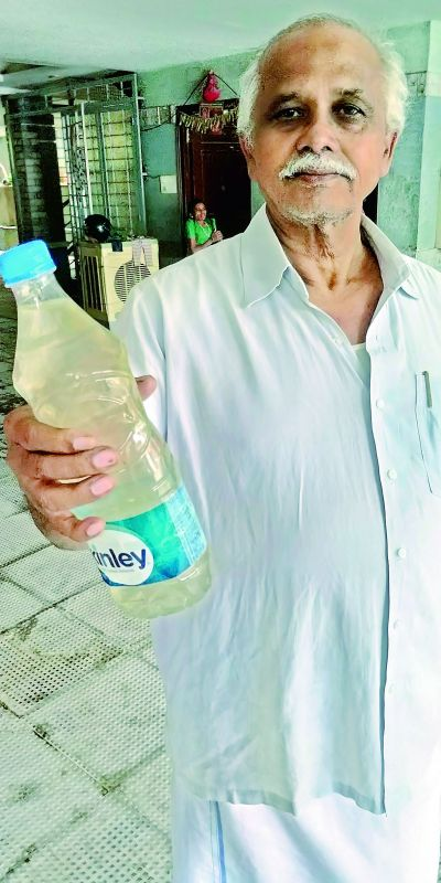 Resident Mohan Rao shows a bottle of contaminated water.
