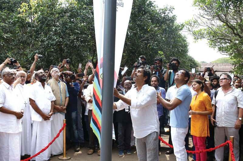 Theatre Director Anamika Haksar (left). Sudarshan Shetty, curator of KMB hoists the KMB flag during the inaugural ceremony