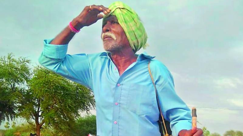A farmer looks to the sky in search of monsoon clouds on Thursday. (Photo: DC)