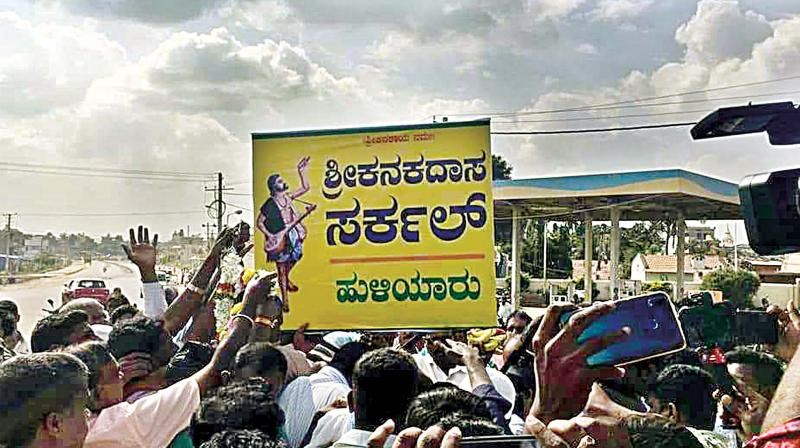 People install Kanakadasa Circle signboard at Huliyaru in Chikkanayakanahalli taluk on Thursday. (Photo: DC)