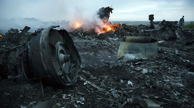 A man walks amongst the debris at the crash site of a passenger plane near the village of Hrabove, Ukraine. (Photo: AP)