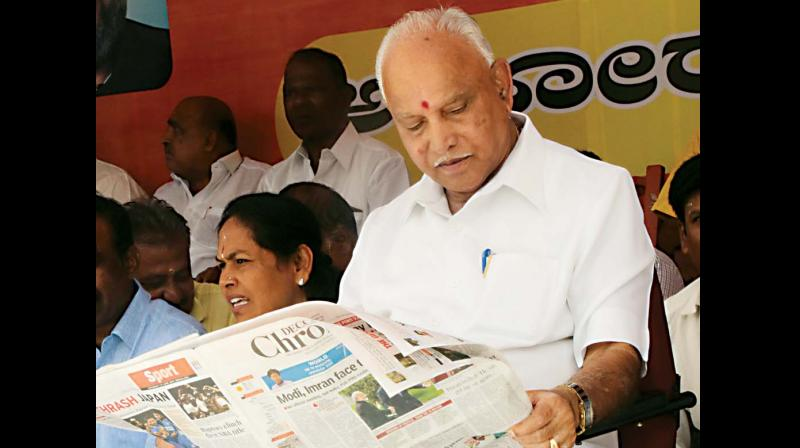 State BJP president B.S. Yeddyurappa updates himself on the day's news with Deccan Chronicle, as he takes part in a dharna. (Photo: DC)