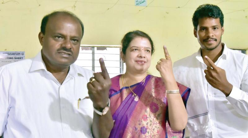 Chief Minister H.D. Kumaraswamy, his wife Anitha and son Nikhil after casting their votes at Ketaganahalli Village, Bidadi taluk, in Ramanagara on Thursday (Photo: KPN)