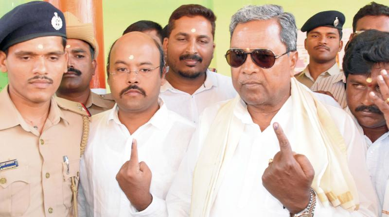 Former CM Siddaramaiah and his son Yathindra after voting at Siddaramana Hundi in Mysuru on Thursday (Photo: KPN)