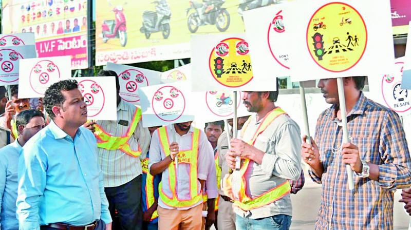 Joint collector Himanshu Shukla gives instructions on how to regulate traffic to traffic rule violators, in Guntur city on Wednesday. As many as 50 traffic rule violators were directed to do community service.  (E. Tejo Roy)