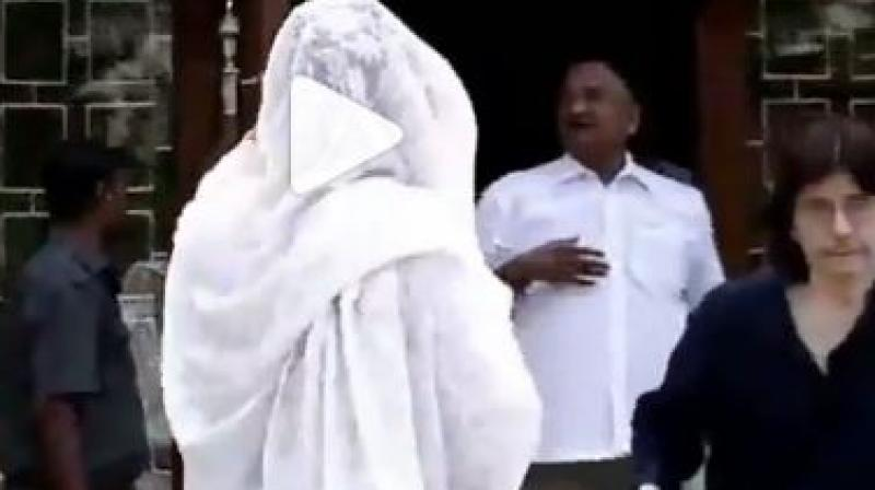 Screenshot from video where Rekha hides herself from the camera.