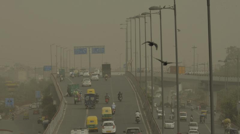 Vehicles ply slowly on a road as dust envelopes the sky over New Delhi, on Wednesday. (Photo: PTI)