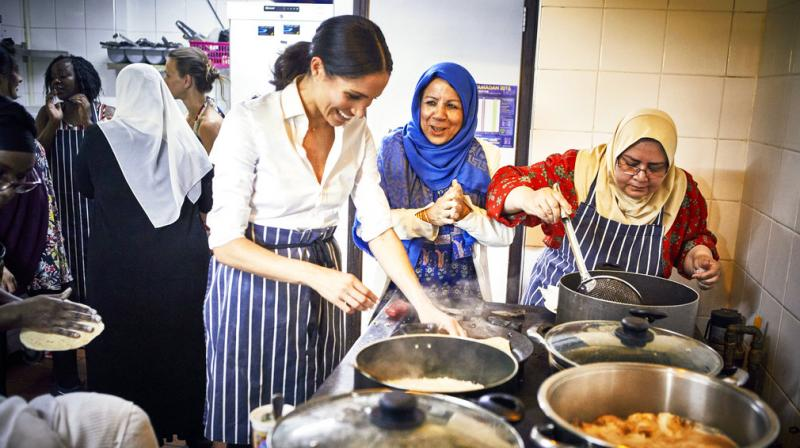 Meghan the Duchess of Sussex cooks with women in the Hubb Community Kitchen at the Al Manaar Muslim Cultural Heritage Centre in London. Set up in the aftermath of the Grenfell Tower fire the community kitchen has resulted in the publication of
