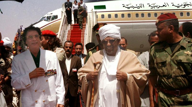 In this May 10, 2001, file photo, Libyan leader Moammar Gadhafi , left, is greeted by President Omar El-Bashir, center, upon his arrival in Khartoum. (Photo:AP)