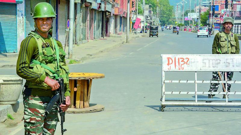Security personnel stand guard at a check point during restrictions in Srinagar on Sunday. 	 (PTI)