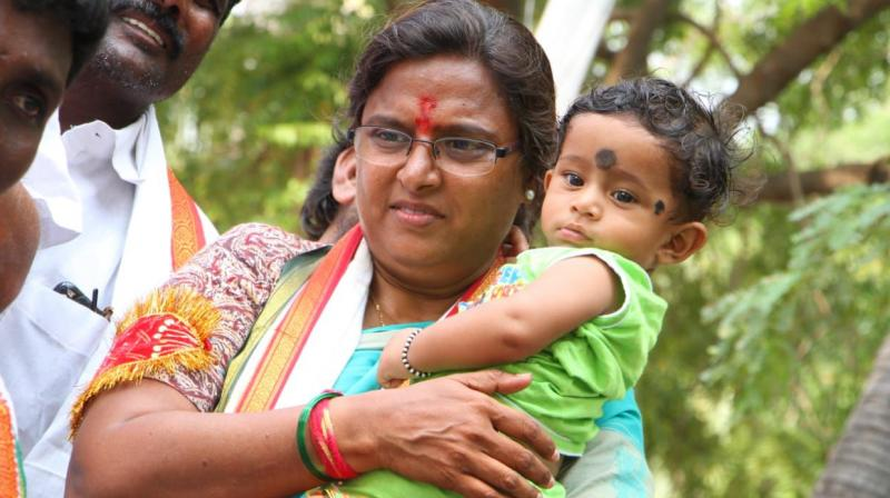 Congress candidate N. Padmavathi Reddy carries a baby during her campaign for the Huzurnagar byelection scheduled for October 21.