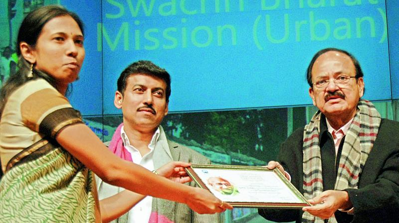 Union minister for urban development M. Venkaiah Naidu hands over the Open Defaecation-free city award under Swachh Bharat to municipal commissioner S. Nagalakshmi in Delhi on Thursday. Minister of state for information and broadcasting Colonel Rajyavardhan Singh Rathore is also seen.