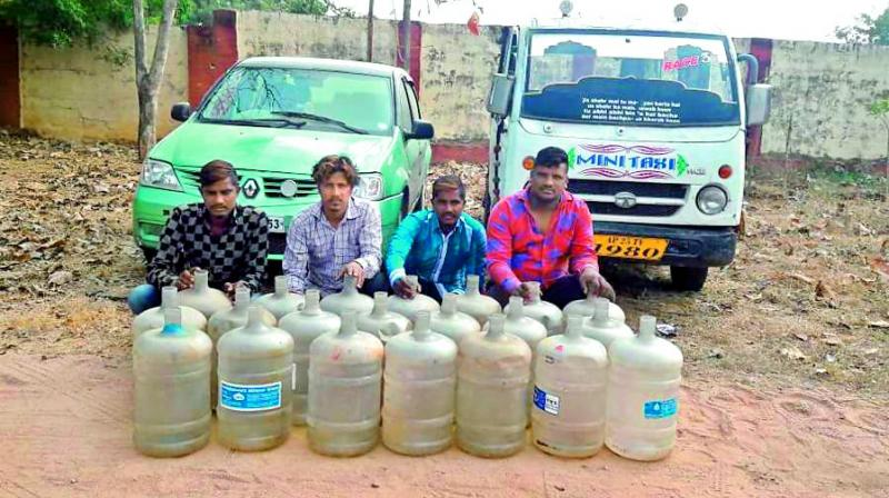 The four accused along with the car and water cans used for stealing diesel.