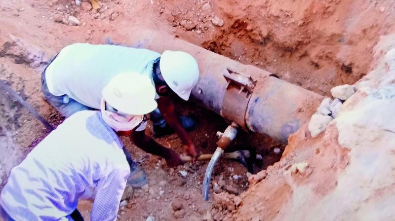 Workers inspect the hole in the pipeline made by the gang to pilfer fuel from it illegally and sell it.