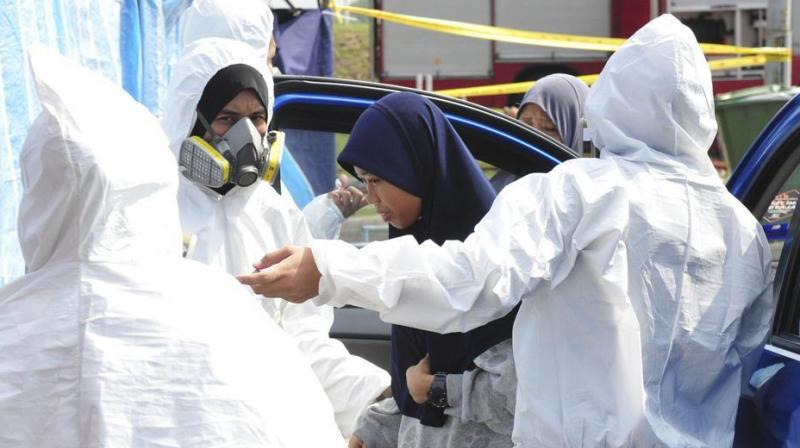 Emergency personnel help a student as she arrives at an evacuation center at Pasir Gudang district in Johor state, Malaysia, Tuesday, June 25, 2019. (Photo: AP)