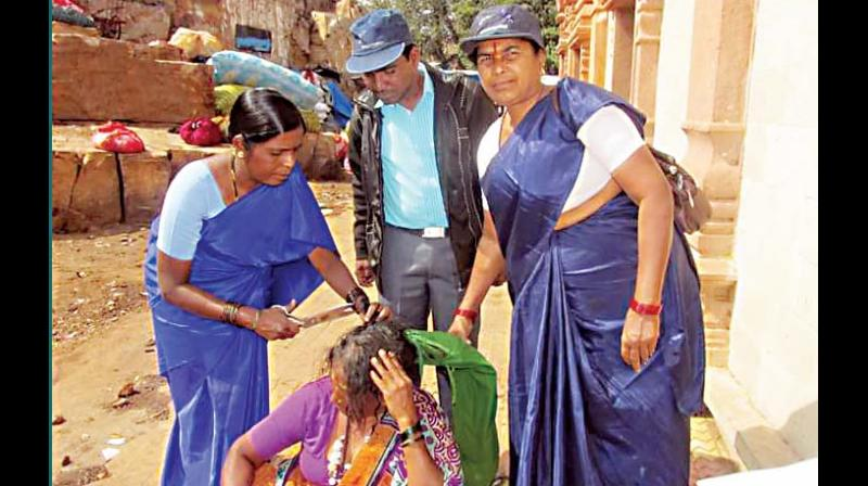 Seetavva Jodatti (left) cutting the hair of a Devadasi as a process of rehabilitation. (Photo: DC)