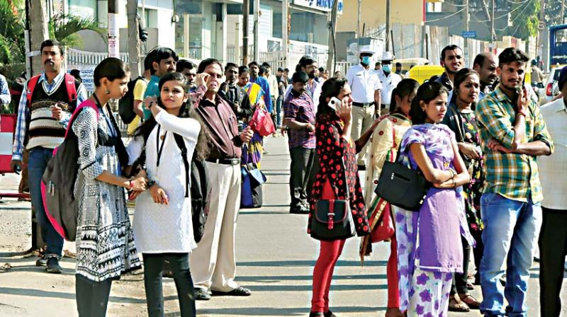 Commuters waiting for BMTC buses in Bengaluru on Wednesday, the second day of the two-day CITU strike 	– KPN