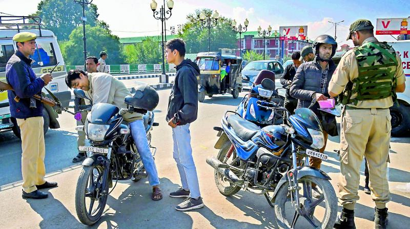 Security personnel check documents of motorcyclists  during a shut down in Srinagar on Sunday.  (PTI)