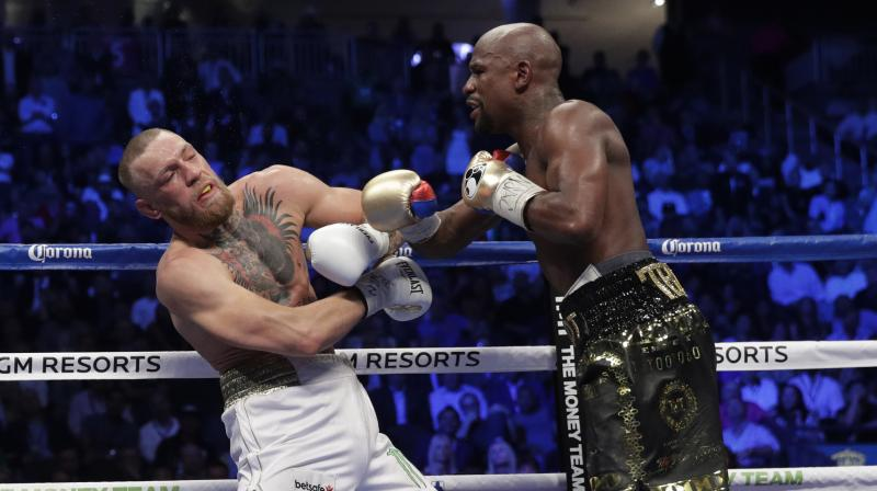 While Conor McGregor (0-1) had the T-Mobile Arena crowd behind his improbable quest, Floyd Mayweather (50-0) survived a rough beginning and gradually took control. (Photo: AP)