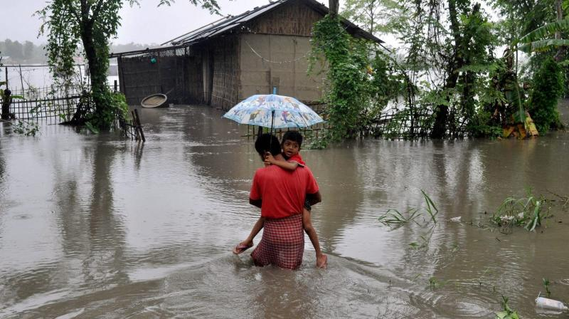 Assam Monsoon flood Lakhimpur: A father carrying his son through the flood water in Lakhimpur, Assam on Saturday. (Photo: PTI)