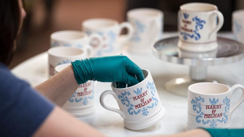 In this file photo taken on April 16, 2018 a worker hand-paints a commemorative mug, with a message celebrating the forthcoming wedding of Britain's Prince Harry and his US fiance Meghan Markle, at the Emma Bridgewater factory in Stoke-on-Trent, central England. (Photo: AFP)