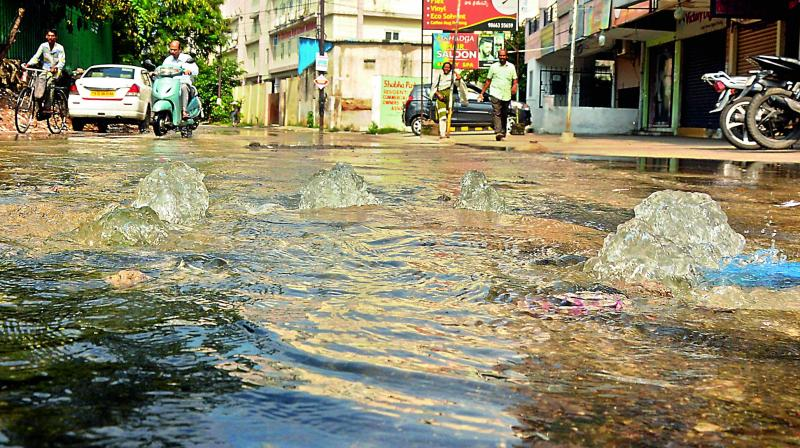 Overflowing water gushes from clogged drains at Vidyanagar even as the area is inundated with rainwater.— Deepak Deshpande