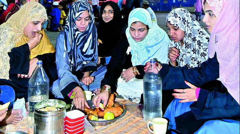 Muslims share food as they break their first fast in the Holy Month of Ramzan at Macca Masjid, Charminar, Hyderabad, on Tuesday. (Image: P. Surendra)