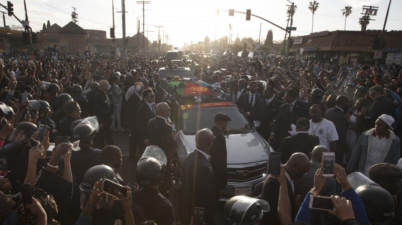 A hearse carrying the casket of slain rapper Nipsey Hussle passes through a large crowd on its 25-mile trek through the streets of the city Thursday. (Photo:AP)