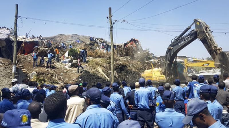 Police officers secure the perimeter at the scene of a garbage landslide, as excavators aid rescue efforts, on the outskirts of the capital Addis Ababa, Ethiopia on Sunday. (Photo: AP)