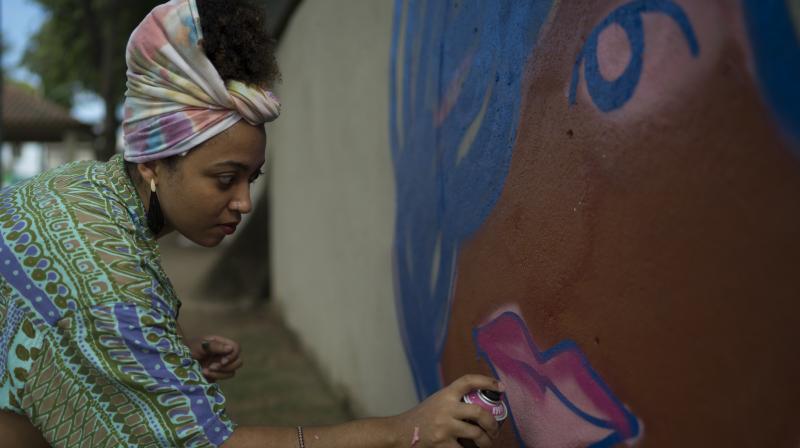 Graffiti artist Maiara Viana Rodrigues paints a mural at her home neighborhood in Rio de Janeiro, Brazil.